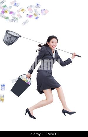 Geschäftsfrau, die Geld mit Schmetterlingsnetz fangen - Stockfoto