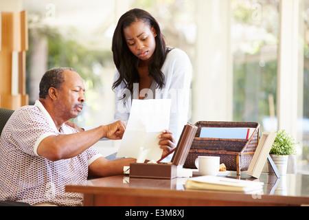 Senior-Vater diskutieren Dokument mit erwachsenen Tochter - Stockfoto