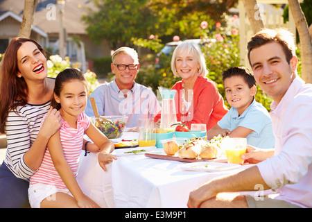 Mehr-Generationen-Familie Mahlzeit im Freien im Garten genießen - Stockfoto