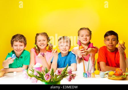 Fünf Kinder halten bunte Ostereier am Tisch - Stockfoto
