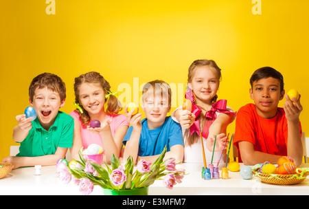 Lustige Kinder mit bunten Ostereiern am Tisch - Stockfoto