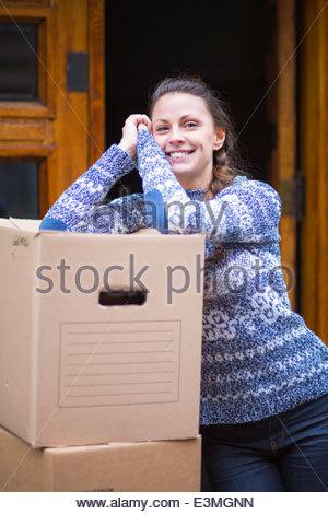 Porträt der glückliche junge Frau stützte sich auf Umzugskartons im freien - Stockfoto