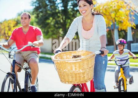 Glückliche Familie Reiten Fahrräder auf sonniger Straße - Stockfoto