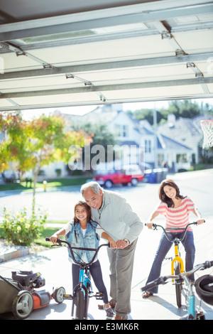 Mehr-Generationen-Familie auf Fahrrädern in Einfahrt - Stockfoto