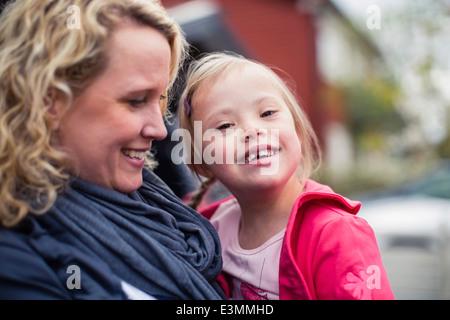 Porträt von fröhliches Mädchen mit Down-Syndrom von Mutter getragen - Stockfoto