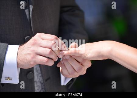 Ein Bräutigam hält, dass seine Frau die hand da er einen Ehering am Finger Bräute während einer traditionellen Hochzeitszeremonie - Stockfoto
