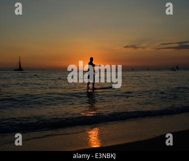 Silhouette Mann auf Stand up Paddle Board während des Sonnenuntergangs - Stockfoto