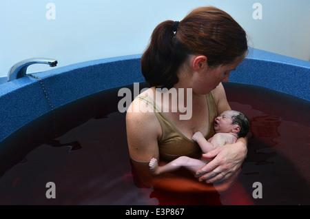 Frau hält ihr Baby in einem Pool nach der natürlichen Geburt. - Stockfoto