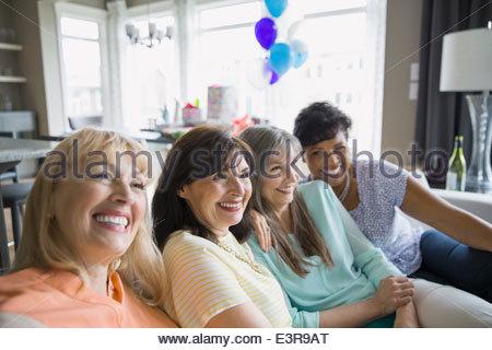Lächelnde Frau auf Sofa im Wohnzimmer - Stockfoto