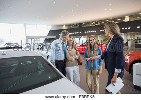 Verkäuferin Übergabe Familie Schlüssel im Autohaus Autohaus - Stockfoto
