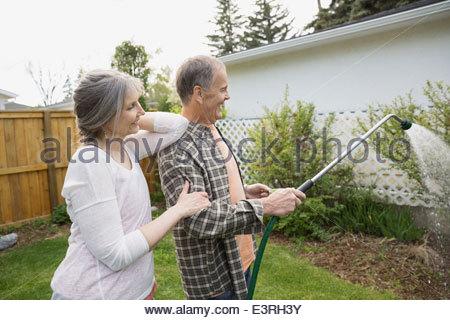 Älteres Paar, die Bewässerung von Pflanzen im Garten - Stockfoto