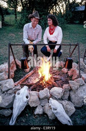 Eine amerikanische Cowboy und seine Freundin starten ein Abend am Lagerfeuer auf seinem Viehranch in der Nähe von - Stockfoto