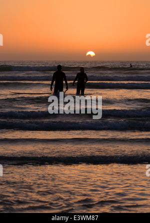 Ein paar den Sonnenuntergang während Surfen in Guernsey