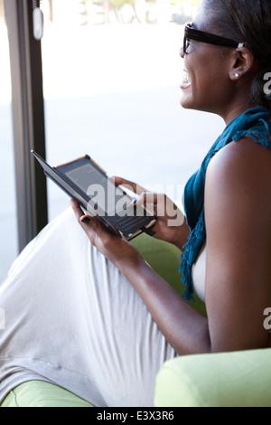 Ethnische Frau lachend in Coffee-Shop ein elektronisches Lesegerät lesen. - Stockfoto