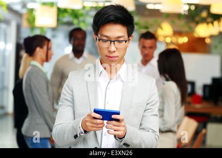 Asiatische Geschäftsmann mit Smartphone vor Kollegen - Stockfoto
