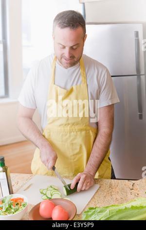 Reifer Mann bereitet frischen Salat in Küche - Stockfoto