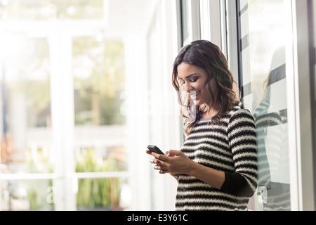 Junge Geschäftsfrau SMS auf Smartphone im Büro - Stockfoto