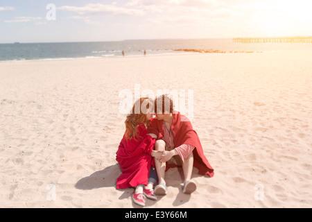 Romantisches Paar eingewickelt in Decken am Strand - Stockfoto
