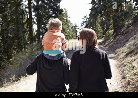Frauen, die zu Fuß durch Wald in Oregon, USA, mit Kleinkind auf Schultern sitzen - Stockfoto