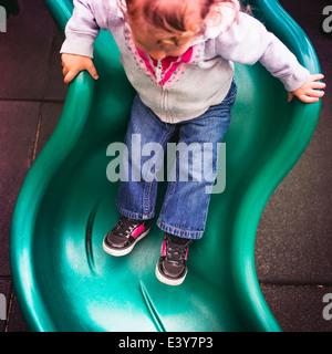 Kleinkind hinunter Folie auf Spielplatz - Stockfoto