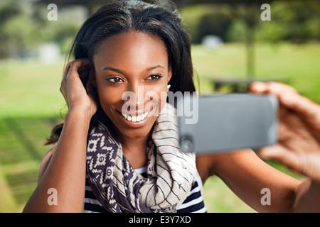 Junge Frau, die die Selbstporträt auf smartphone - Stockfoto
