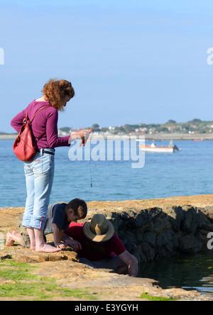 Familie Angeln für Krebse ab Anlegestelle in Guernsey, Channel Islands, GB - Stockfoto