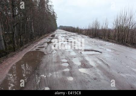 Gebrochene Asphaltstraße mit Löcher und Pfützen, Russland - Stockfoto