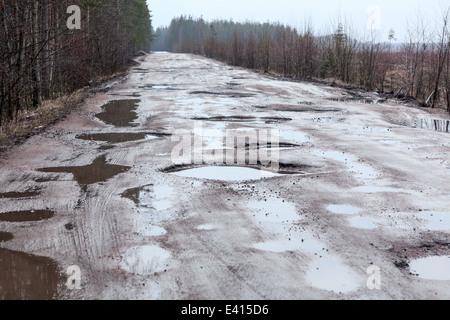 Gebrochene Asphaltstraße in Wäldern mit Löcher und Pfützen, Russland - Stockfoto