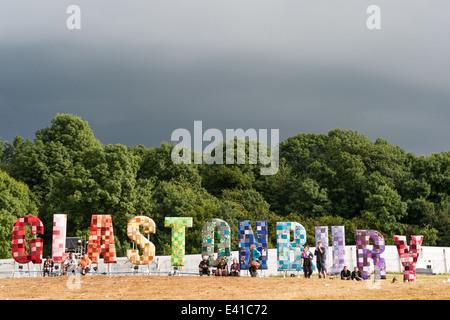 GLASTONBURY, UK - 28 Juni: Festival-Gänger Blick auf ein Panorama über das Festival mit einem großen Schild von - Stockfoto