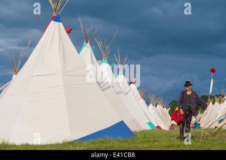 GLASTONBURY, UK - 28 Juni: A Festivalbesucher steht durch eine Reihe von Tipi-Zelte beim Glastonbury Festival am - Stockfoto
