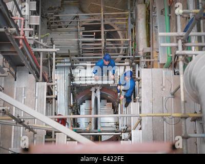Porträt von Ingenieuren arbeitet tief unten in der Ausrüstung während Kraftwerk Ausfalls, erhöhte Ansicht - Stockfoto