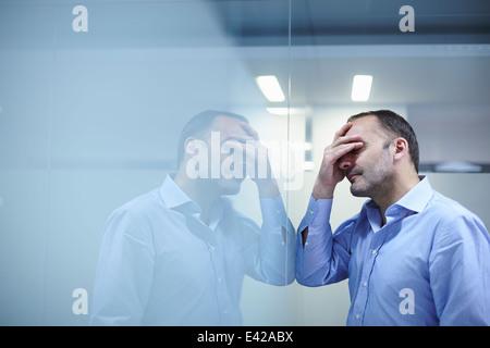 Mann verzweifelt vor reflektierenden Wand - Stockfoto