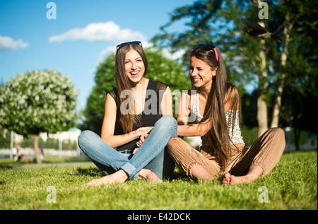 Zwei junge Frauen beste Freunde Lachen im park - Stockfoto