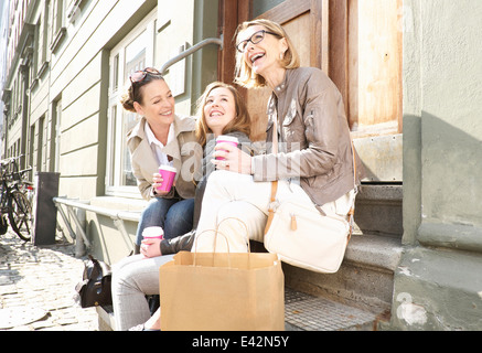 Drei Generationen Frauen trinken Kaffee zum mitnehmen auf Straße - Stockfoto
