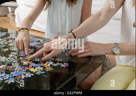 Hände von Mutter und Tochter tut Jigsaw puzzle - Stockfoto