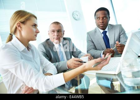 Porträt von hübschen Sekretärin zeigt auf Laptop-Bildschirm etwas zu ihrem Chef und Kollegen zu erklären - Stockfoto