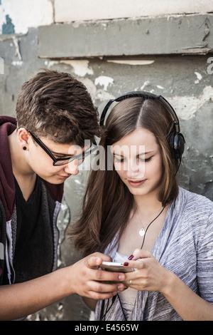 Teenager-paar Musikhören auf smartphone - Stockfoto