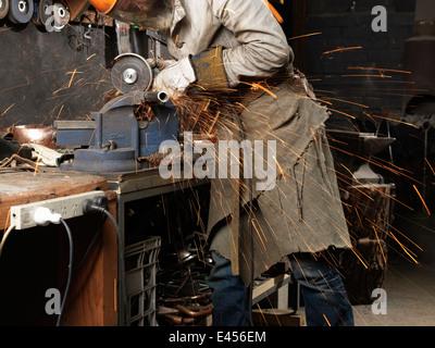 Schleifen von Metall auf einer Maschine im Workshop Schmied - Stockfoto