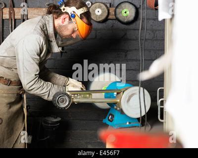 Schmiede arbeiten an Maschine in Werkstatt - Stockfoto