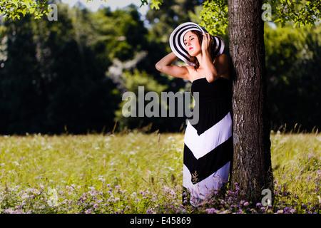 Eine schöne junge Frau in der Sonne aalen, wie sie an einen Baum lehnt. - Stockfoto