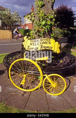 Yorkshire, Vereinigtes Königreich. 2. Juli 2014. Radfahrer vorbei an gelben Penny Farthing Fahrrad in das Dorf von - Stockfoto