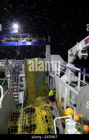 Trawlerman ausbessern Netze des Fischereifahrzeugs Schleppnetz Deck während einer winterlichen Nacht an der Nordsee, - Stockfoto