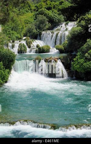 Krka Fluss fließt über eine Reihe von Travertin Dämme oder Hindernisse am Skradinski Buk Wasserfall, mit dicht bewaldete - Stockfoto