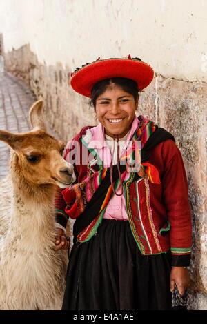 Porträt eines Mädchens Quechua in traditioneller Tracht mit einem Lama, Cuzco, Peru, Südamerika