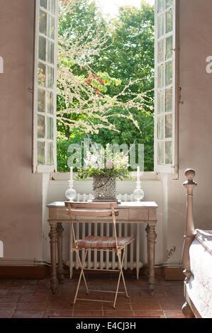Französischen Café Stil Stuhl von hölzernen Schreibtisch im Schlafzimmer mit gefliesten Terrakotta-Böden und hohen - Stockfoto