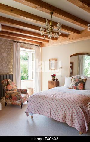 Antike Persische bestickte Quilt auf Bett im Schlafzimmer mit Steinmauern und Holzbalken. Der Sessel ist in fl gepolstert. - Stockfoto