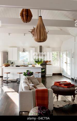 Weiße offene Wohnraum mit Holzfurnier Beleuchtung, Ikea Küche Einheiten und moderne Creme sofa - Stockfoto
