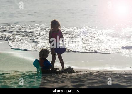 Die Silhouetten der beiden Kinder am Strand spielen, wenn die Sonne in St. Croix, Amerikanische Jungferninseln untergeht. - Stockfoto