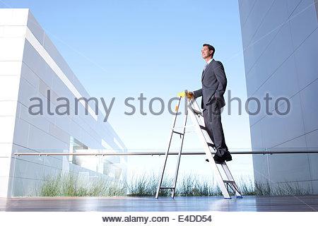 Geschäftsmann auf Leiter auf Balkon stehend - Stockfoto