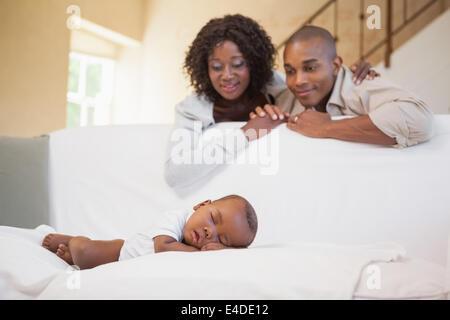 Babyjungen schlafen friedlich auf Couch beobachtet von Eltern - Stockfoto
